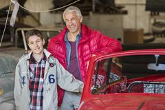 Portrait smiling father and son next to classic car in auto repair shop Stock Photos