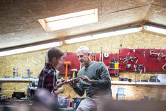 Father explaining tool to son in auto repair shop Stock Photos