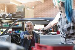 Mechanic reaching for tool in auto repair shop Stock Photos