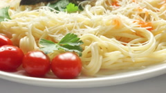 Spaghetti with parmesan and basil on a white plate Stock Footage