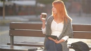 Girls with red hair sitting on a bench at the street and drink coffee, young Stock Footage