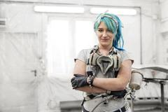 Portrait confident young woman with blue hair with paint gun in auto body shop Stock Photos