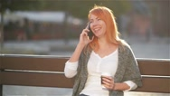Beautiful woman with red hair talking on the mobile phone sitting on a bench in Stock Footage
