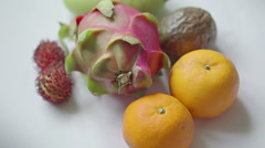 Assorted tropical fruit: rambutan, mango, dragon fruit, passionfruit, tangerine Stock Footage