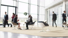 4K Businessmen greet each other in meeting area of large modern office building Stock Footage