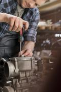 Mechanic fixing car engine at auto repair shop Stock Photos