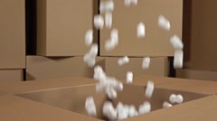 Pouring soft polystyrene pieces into big carton. Shockproof packaging material Stock Footage