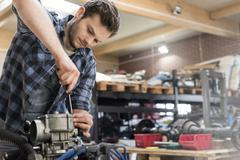 Mechanic fixing car engine in auto repair shop Stock Photos
