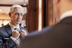Businessman trying on tie in mirror in menswear shop Stock Photos