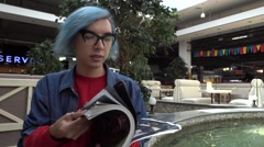 Transgender Gay with blue Hair turns glamorous Fashion Magazine at the Mall Stock Footage