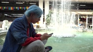 Transgender Gay with blue Hair sitting sadly alone - Mobile Phone in Hand chatin Stock Footage