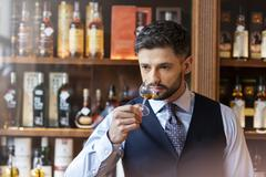 Well-dressed man whiskey tasting Stock Photos