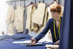 Female tailor cutting fabric in menswear workshop Stock Photos