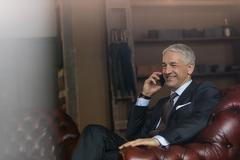 Smiling businessman talking on cell phone in menswear shop Stock Photos