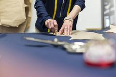 Female tailor marking fabric with pattern in menswear workshop Stock Photos