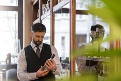 Well-dressed bartender examining whiskey bottle Stock Photos