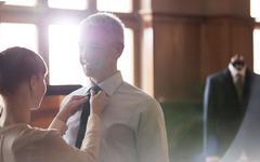 Tailor adjusting tie for businessman in menswear shop Stock Photos