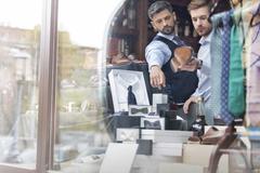 Worker showing businessman merchandise in window of menswear shop Stock Photos