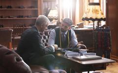 Tailor and businessman talking in menswear shop Stock Photos