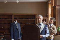 Tailor fitting businessman for suit in menswear shop Stock Photos