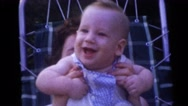 1954: a woman holding up a sweet smiling baby in her hands in front of her Stock Footage