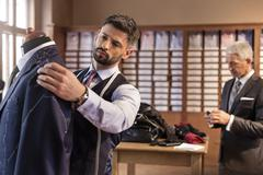 Tailor adjusting suit on dressmakers model in menswear shop Stock Photos