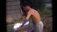 1954: a shirtless man in shorts folding aluminum foil and placing it on a fire Stock Footage