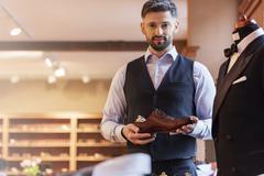 Portrait confident businessman holding dress shoe in menswear shop Stock Photos