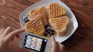 Top view woman photographing breakfast using mobile phone Belgian waffles Stock Footage