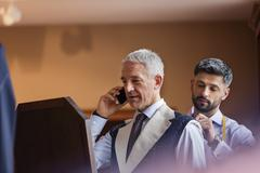 Tailor fitting businessman on cell phone for suit in menswear shop Stock Photos