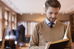 Tailor taking notes in notebook in menswear shop Stock Photos