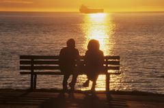 Couple on bench enjoying the sunset, Stanley Park, English Bay, Vancouver, Stock Photos