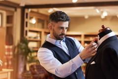 Tailor adjusting tie on dressmakers model in menswear shop Stock Photos