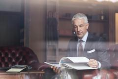 Businessman browsing book in menswear shop Stock Photos