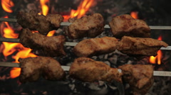 Tasty shashlik is prepared on skewer in an open fire Stock Footage