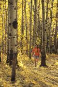 Young asian woman trail running below Mt Yamnuska, Kananaskis, Alberta, Canada. Stock Photos