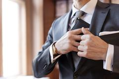 Close up businessman retrieving wallet from suit jacket Stock Photos