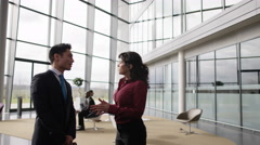 4K Business man & woman talking in busy meeting area of large modern office Stock Footage