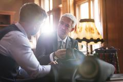 Tailor and businessman discussing suit in menswear shop Stock Photos