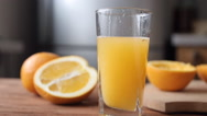 Orange juice pouring in glass on color background Stock Footage