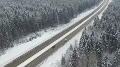Road in the winter forest with driving cars. Aerial view. Vanishing perspective. Stock Footage
