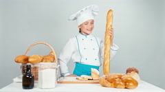 Baker girl 7-8 years child gives you bread baguettes and smiling at camera Stock Footage