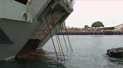 Amphibious armored assault vehicles are driven across a bay and onto a ship. Stock Footage