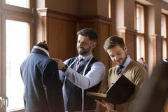 Tailors examining suit and taking notes in menswear shop Stock Photos