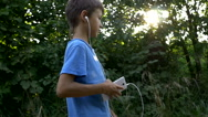Boy walking down the street uses the phone and listening to music Stock Footage