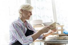 Smiling woman examining pottery in studio Stock Photos