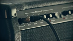 Plugging cord to guitar amplifier Stock Footage
