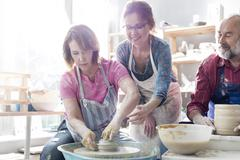 Teacher guiding mature student using pottery wheel in studio Stock Photos