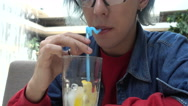 Transgender Gay with blue Hair drinking Mojito Cocktail at the Mall Stock Footage