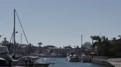 Zoom out on a Small finger in the harbor oceanfront homes with their yachts a Stock Footage